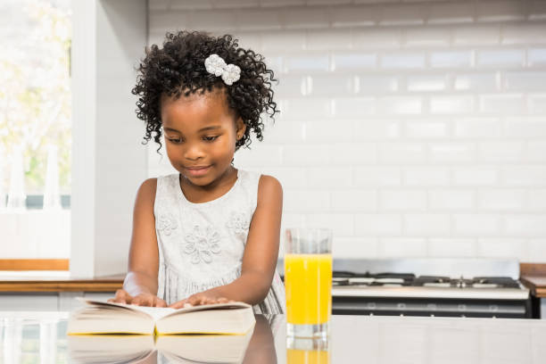 Smiling girl reading a book in the kitchen